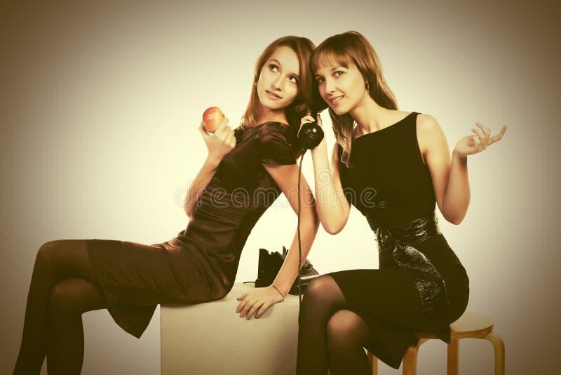 Duas mulheres novas felizes da forma que chamam o telefone retro fotografia de stock