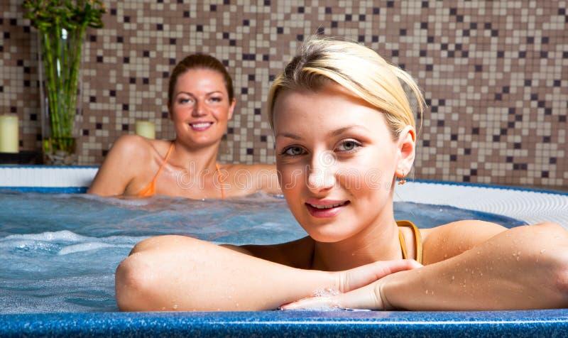Duas mulheres novas na cuba quente foto de stock