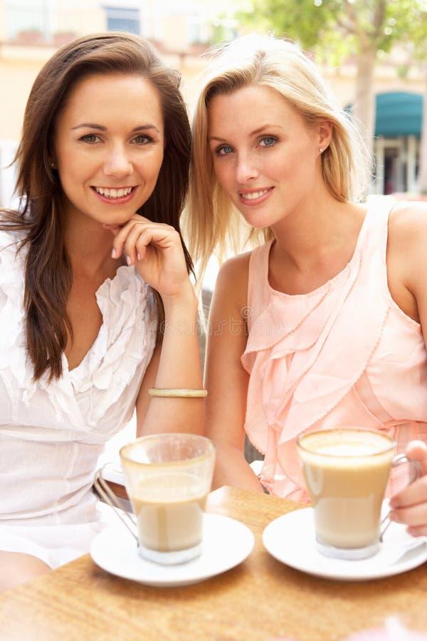 Duas mulheres novas que apreciam a chávena de café fotos de stock royalty free