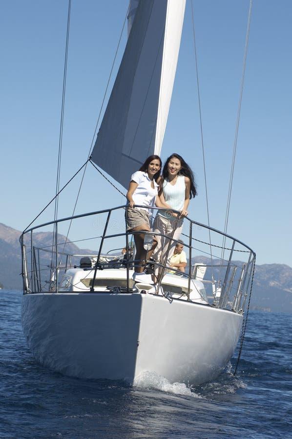 Duas mulheres novas que estão na curva do sailboat imagem de stock