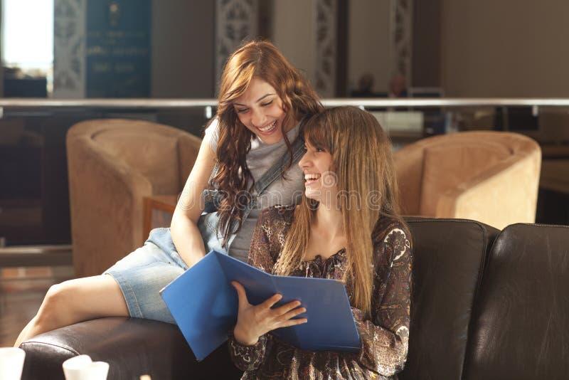 Duas mulheres novas que olham o menue imagens de stock