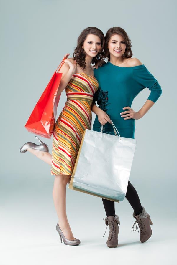 Duas mulheres novas que prendem alguns sacos de compra foto de stock