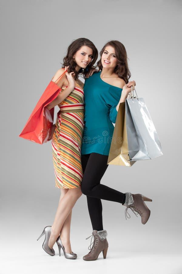 Duas mulheres novas que prendem alguns sacos de compra imagem de stock