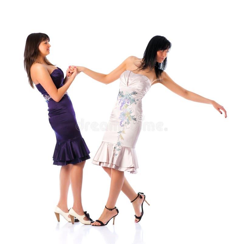 Duas mulheres novas que prendem as mãos imagens de stock royalty free