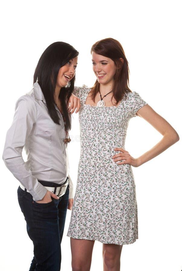 Duas mulheres novas que sussurram a cada um imagem de stock
