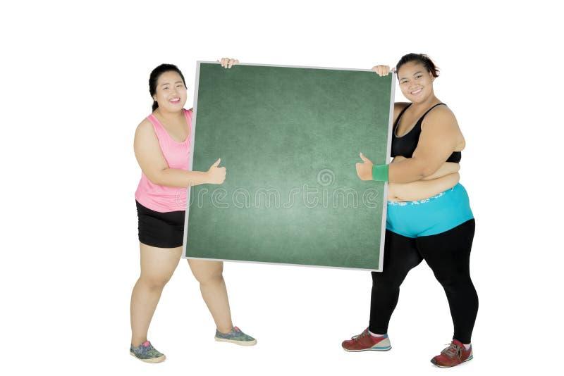 Duas mulheres obesos com o quadro no estúdio imagens de stock