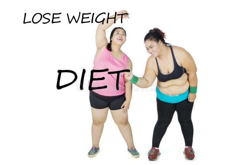 Duas mulheres obesos que escrevem seus objetivos fotografia de stock royalty free