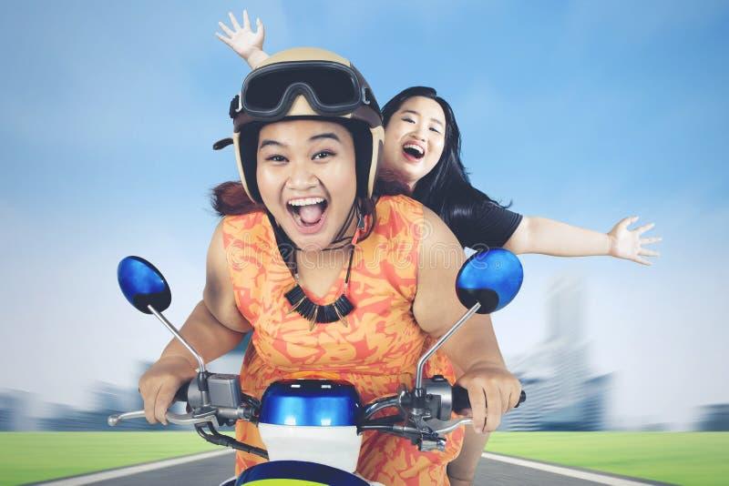 Duas mulheres obesos que montam o 'trotinette' ao longo da estrada de cidade fotografia de stock royalty free