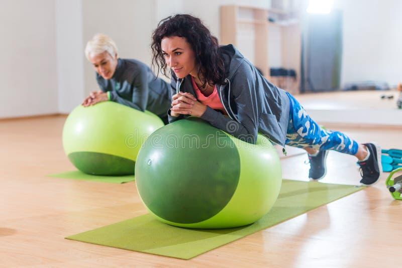 Duas mulheres positivas que fazem a prancha exercitam o encontro na bola do equilíbrio no gym fotos de stock royalty free