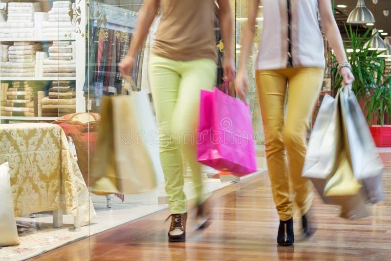 Duas mulheres que andam ao longo das janelas da loja com os sacos de compras nas mãos imagens de stock