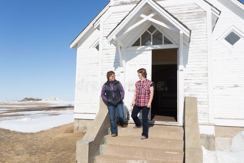 Duas mulheres que andam fora de um riso da igreja imagem de stock royalty free