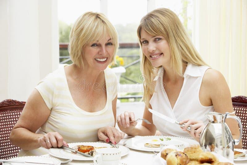 Duas mulheres que apreciam o pequeno almoço do hotel fotografia de stock