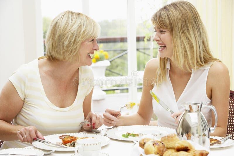 Duas mulheres que apreciam o pequeno almoço do hotel fotos de stock