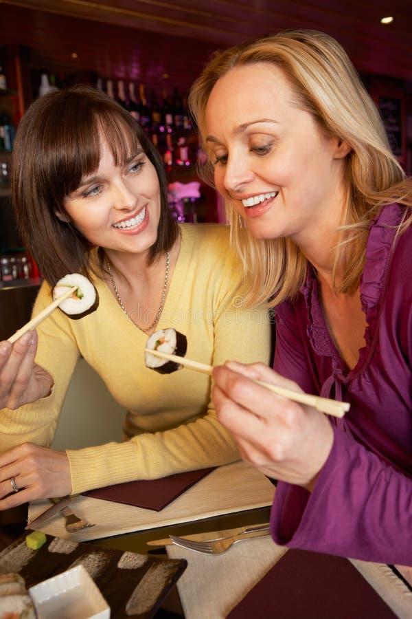 Duas mulheres que apreciam o sushi no restaurante fotos de stock