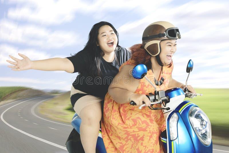 Duas mulheres que apreciam sua viagem com uma motocicleta imagem de stock