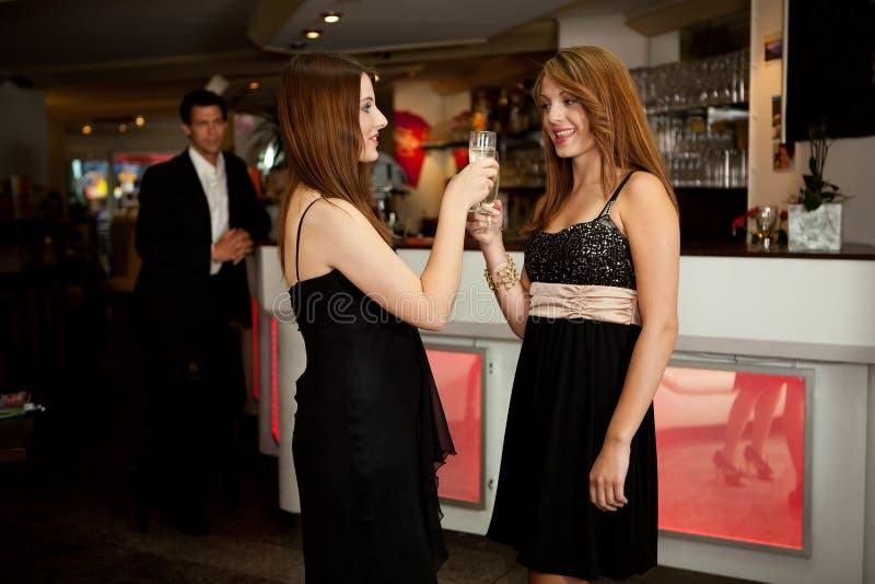 Duas mulheres que clinking vidros foto de stock