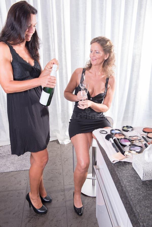 Duas mulheres que comem uma garrafa do champanhe fotografia de stock royalty free