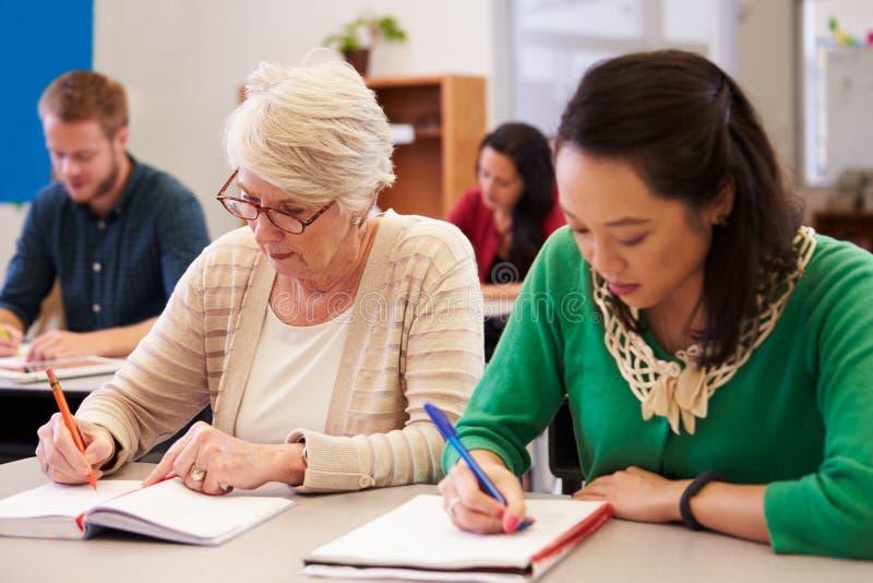 Duas mulheres que compartilham de uma mesa em uma classe do ensino para adultos imagem de stock royalty free