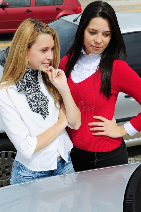 Duas mulheres que compram um carro novo imagens de stock