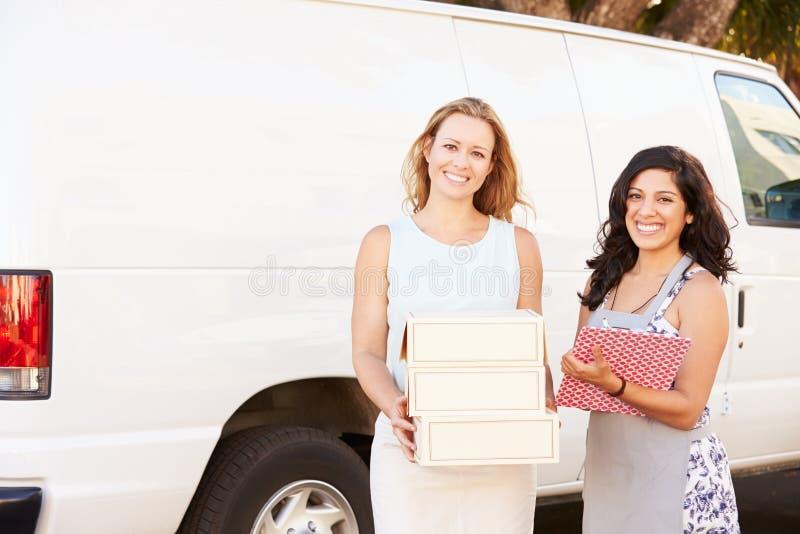 Duas mulheres que correm o negócio de restauração com Van imagem de stock royalty free
