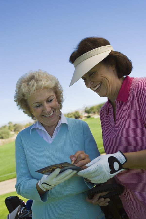 Duas mulheres que escrevem no cartão da contagem no campo de golfe foto de stock royalty free