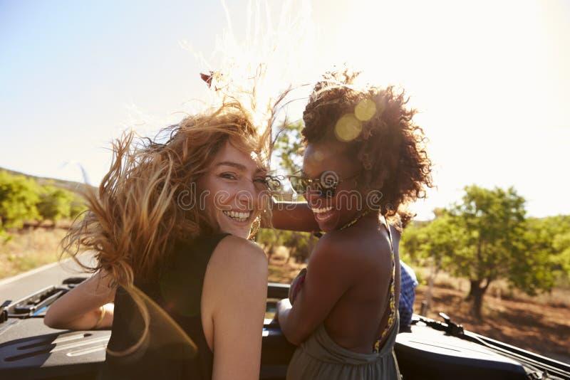 Duas mulheres que estão na parte de trás do carro aberto que gira para a câmera fotos de stock royalty free