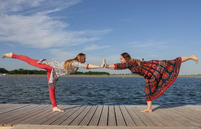 Duas mulheres que exercitam no parque Mulher bonita nova que faz exerc?cios junto fora imagem de stock