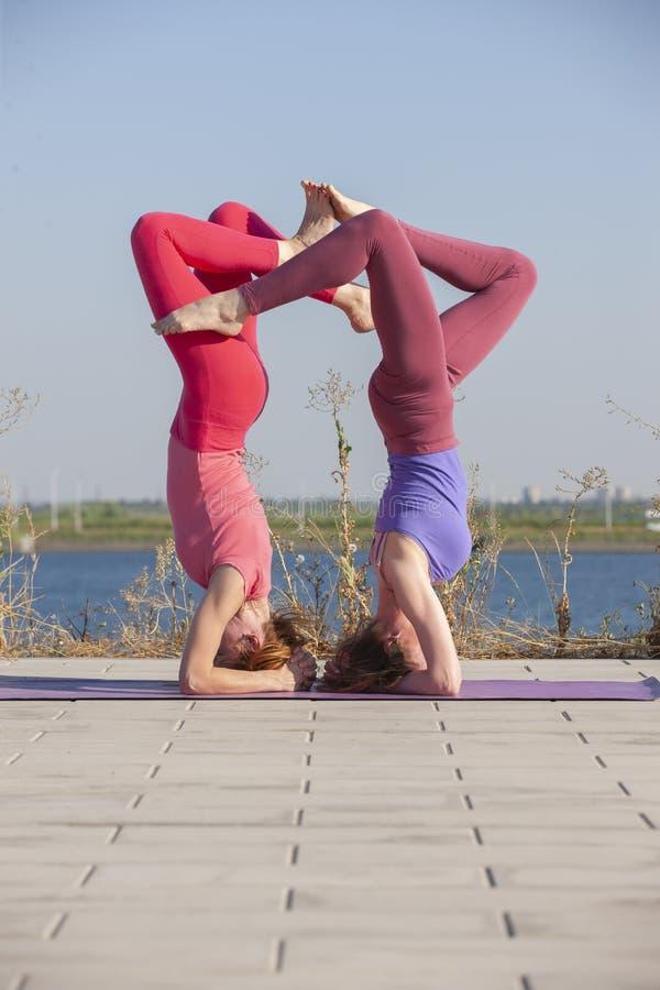Duas mulheres que exercitam no parque Mulher bonita nova que faz exerc?cios junto fora fotos de stock royalty free