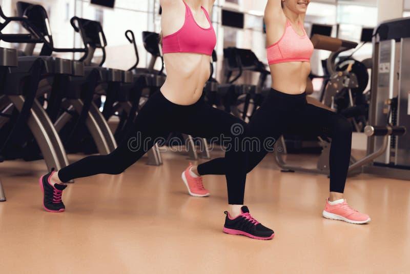 Duas mulheres que fazem exercícios aeróbios no gym Olham felizes, elegantes e aptos foto de stock royalty free