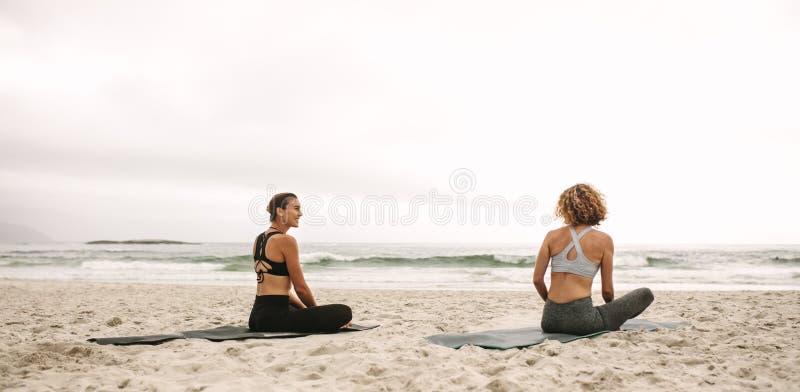 Duas mulheres que fazem a ioga que senta-se na praia fotos de stock royalty free
