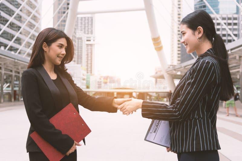 Duas mulheres que fazem o aperto de mão que cumprimenta-se na reunião de grupo no ar livre Executivos e contrato do negócio Amiza imagens de stock