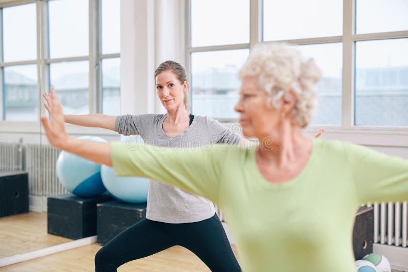 Duas mulheres que fazem o exercício do esticão e da ginástica aeróbica fotos de stock