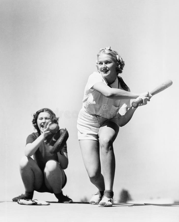 Duas mulheres que jogam o basebol (todas as pessoas descritas não são umas vivas mais longo e nenhuma propriedade existe Garantia fotografia de stock