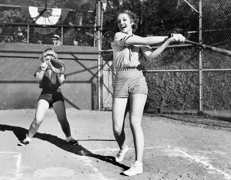 Duas mulheres que jogam o basebol (todas as pessoas descritas não são umas vivas mais longo e nenhuma propriedade existe Garantia imagem de stock royalty free