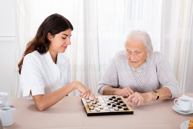 Duas mulheres que jogam o jogo dos verificadores foto de stock royalty free