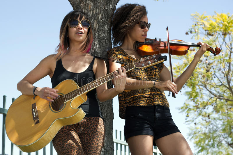 Duas mulheres que jogam uma guitarra e um violino ao lado da árvore imagem de stock
