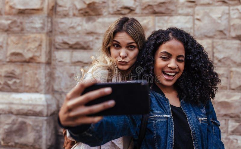 Duas mulheres que levantam para um selfie fora imagem de stock