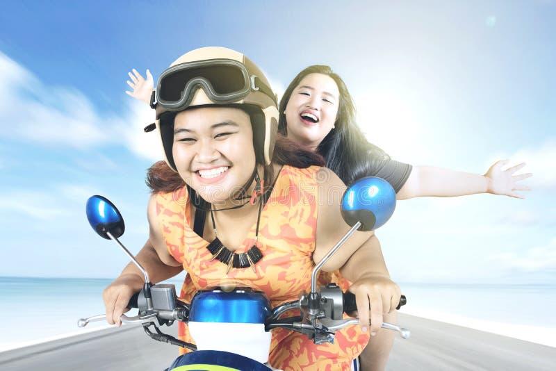 Duas mulheres que montam uma motocicleta à praia foto de stock