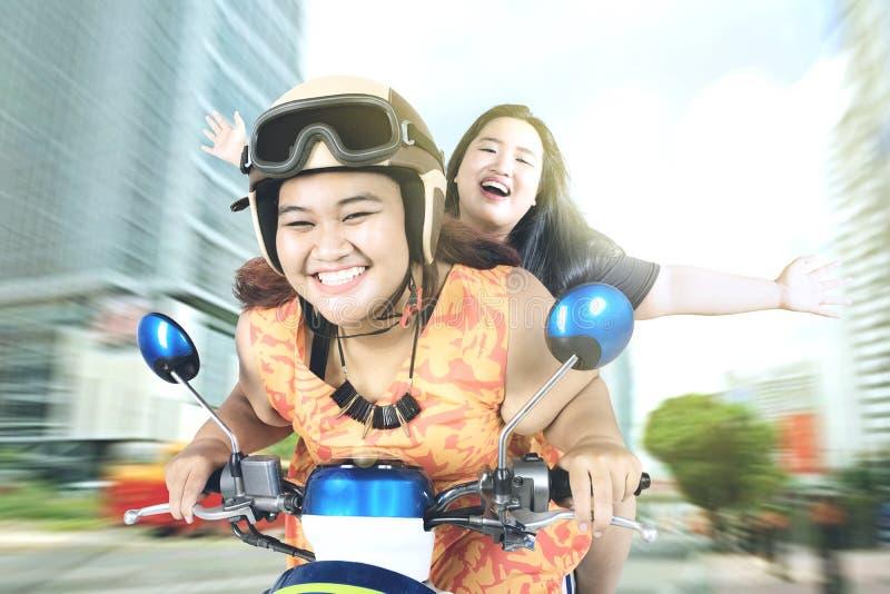 Duas mulheres que montam uma motocicleta na cidade fotos de stock