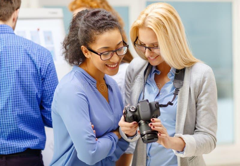 Duas mulheres que olham a câmara digital no escritório foto de stock royalty free