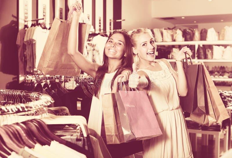 Duas mulheres que olham entusiasmado e que levam muitos sacos de papel no fashio fotos de stock royalty free