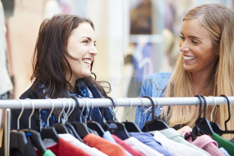 Duas mulheres que olham a roupa no trilho no shopping fotos de stock