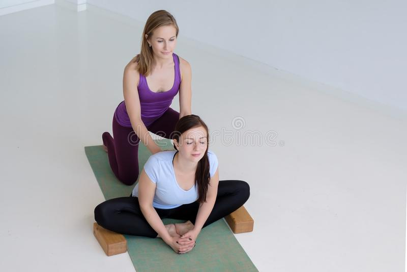 Duas mulheres que praticam a ioga, fazendo o exercício da borboleta, konasana do baddha com suportes fotografia de stock