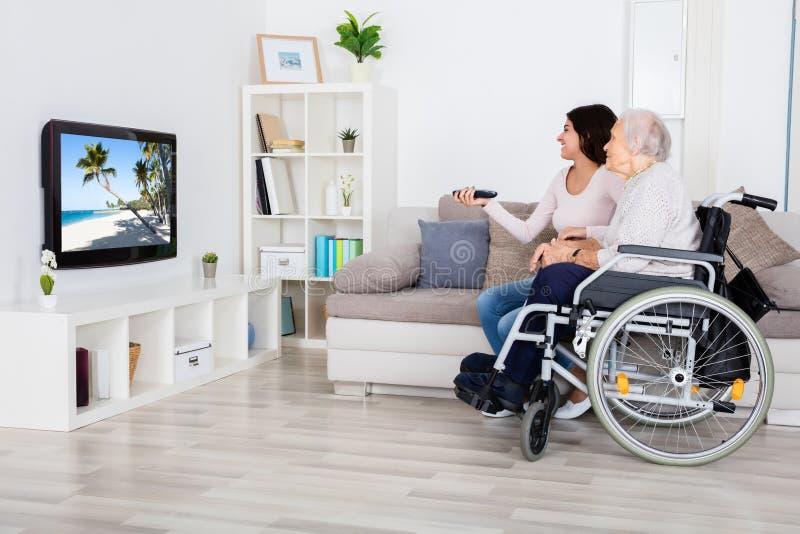 Duas mulheres que prestam atenção à televisão em casa imagens de stock