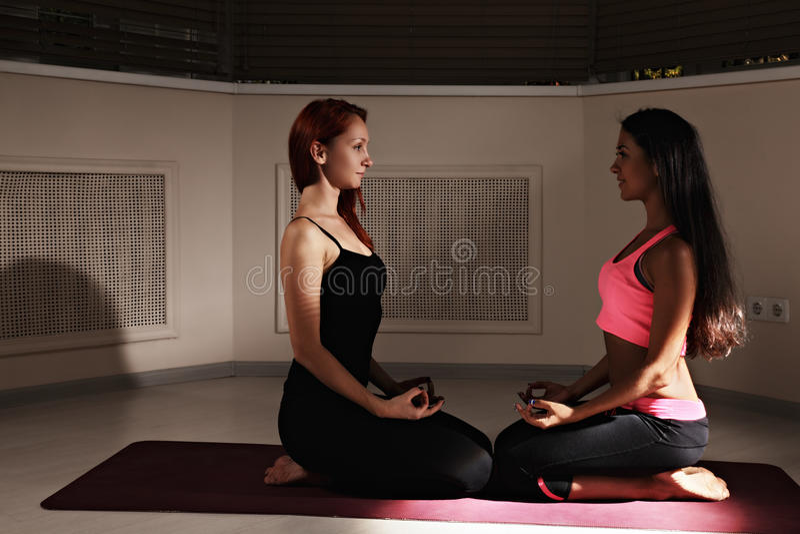 Duas mulheres que relaxam na classe escura da ioga imagem de stock
