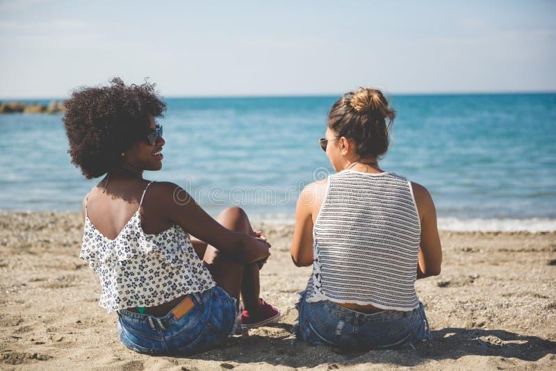 Duas mulheres que relaxam na fala da praia imagem de stock