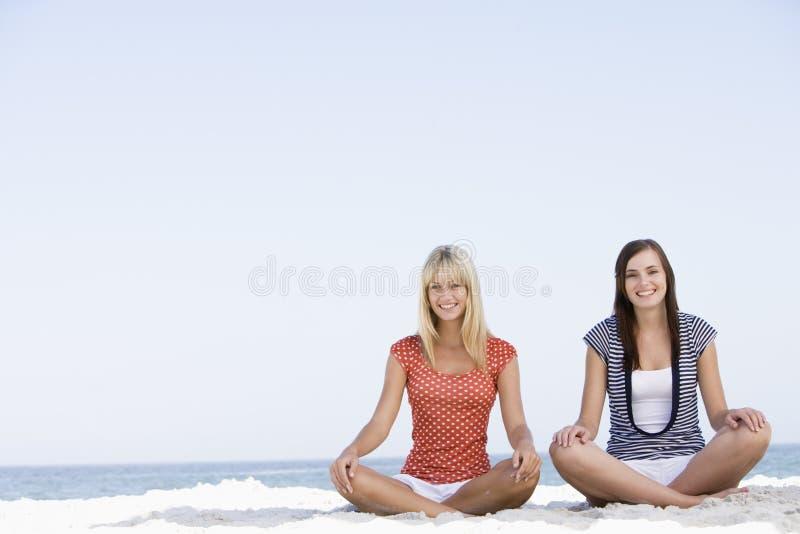 Duas mulheres que sentam-se na praia fotografia de stock