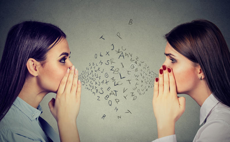 Duas mulheres que sussurram um segredo da bisbolhetice entre si com alfabeto rotulam in-between imagens de stock royalty free