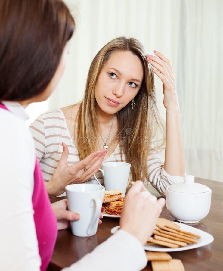 Duas mulheres que têm a fala séria na tabela imagens de stock