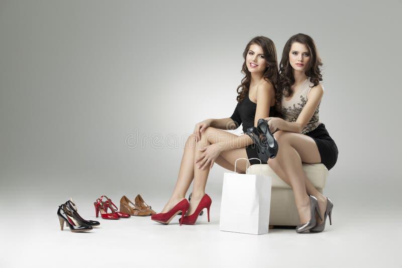 Duas mulheres que tentam os saltos elevados fotografia de stock royalty free